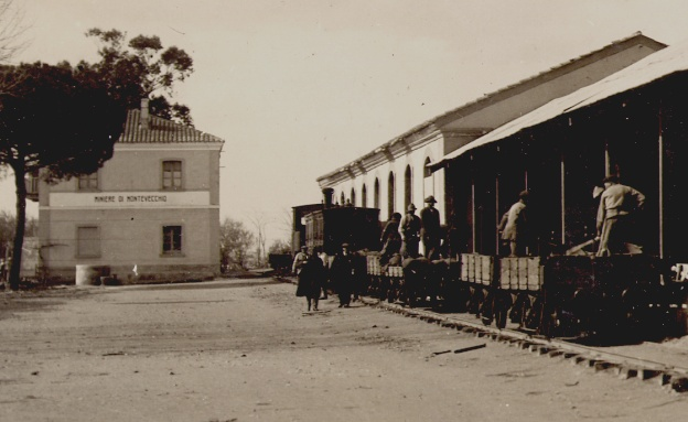"""Montevecchio: le operazioni di scarico del treno giunto a San Gavino; nello sfondo il fabbricato con la scritta """"Miniere di Montevecchio""""."""